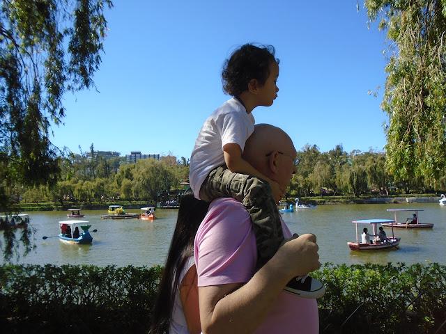 Boy riding on dad shoulder around Burnham Park