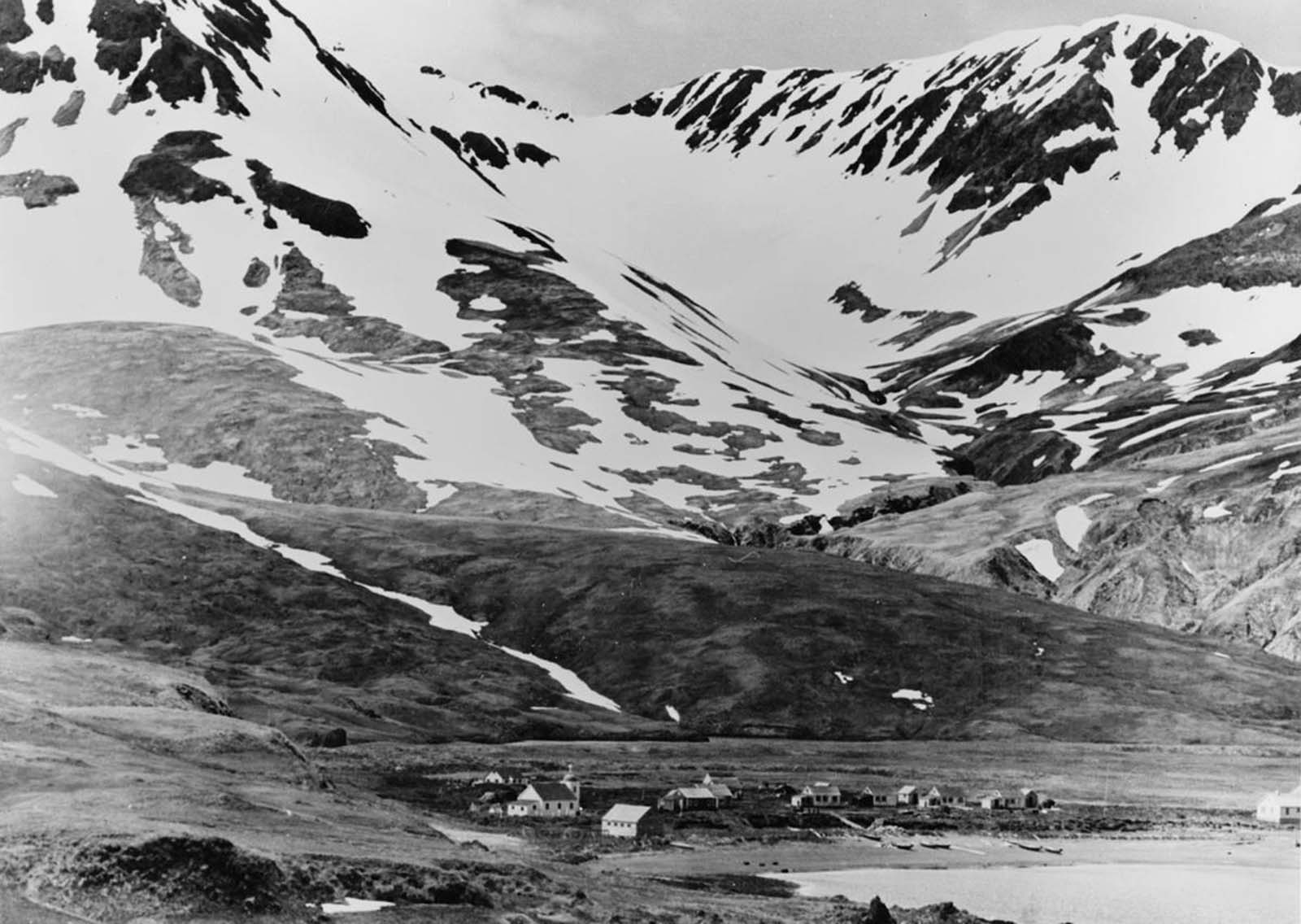 Bleak, mountainous Attu Island in Alaska had a population of only about 46 people prior to the Japanese invasion. On June 6, 1942, a Japanese force of 1,100 soldiers landed, occupying the island. One resident was killed in the invasion, the remaining 45 were shipped to a Japanese prison camp near Otaru, Hokkaido, where sixteen died while in captivity. This is a picture of Attu village situated on Chichagof Harbor.