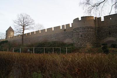 Ein Stück Stadtmauer. Im Hintergrund ein turmartiges Gebäude, die frühere Gereonsmühle.