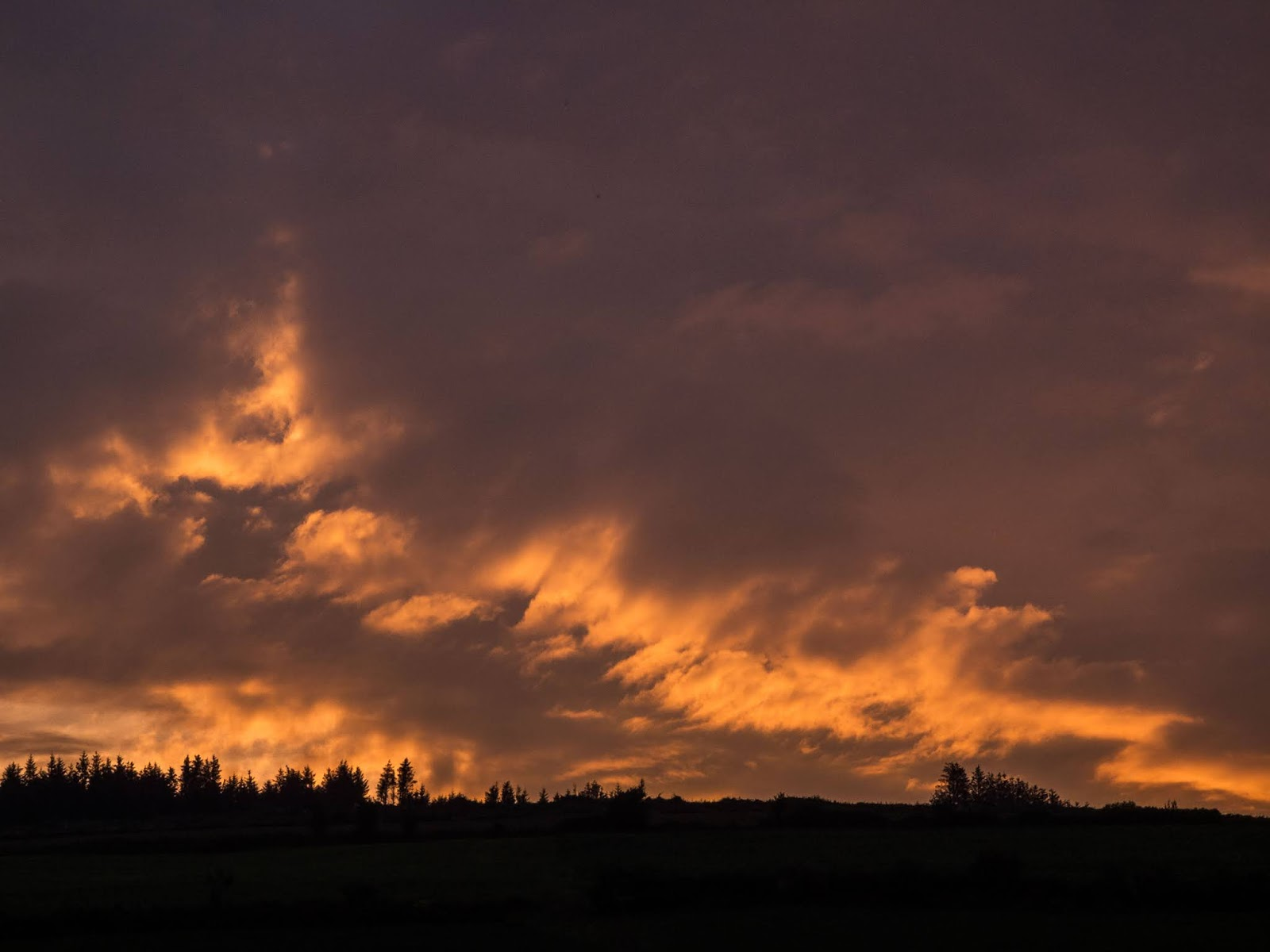 Dark and fiery looking clouds at sunset over a hill in the Boggeragh Mountains, Co.Cork.