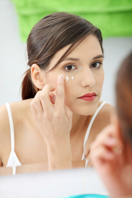 woman in mirror adding eye cream