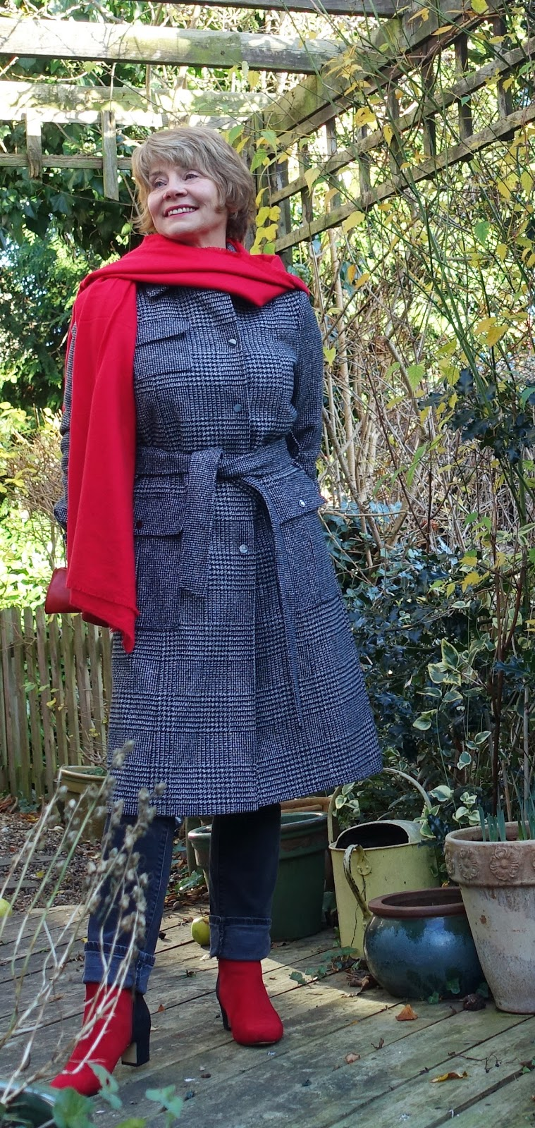 Image showing an over 50 woman in buttoned up check coat and red scarf in winter 2017