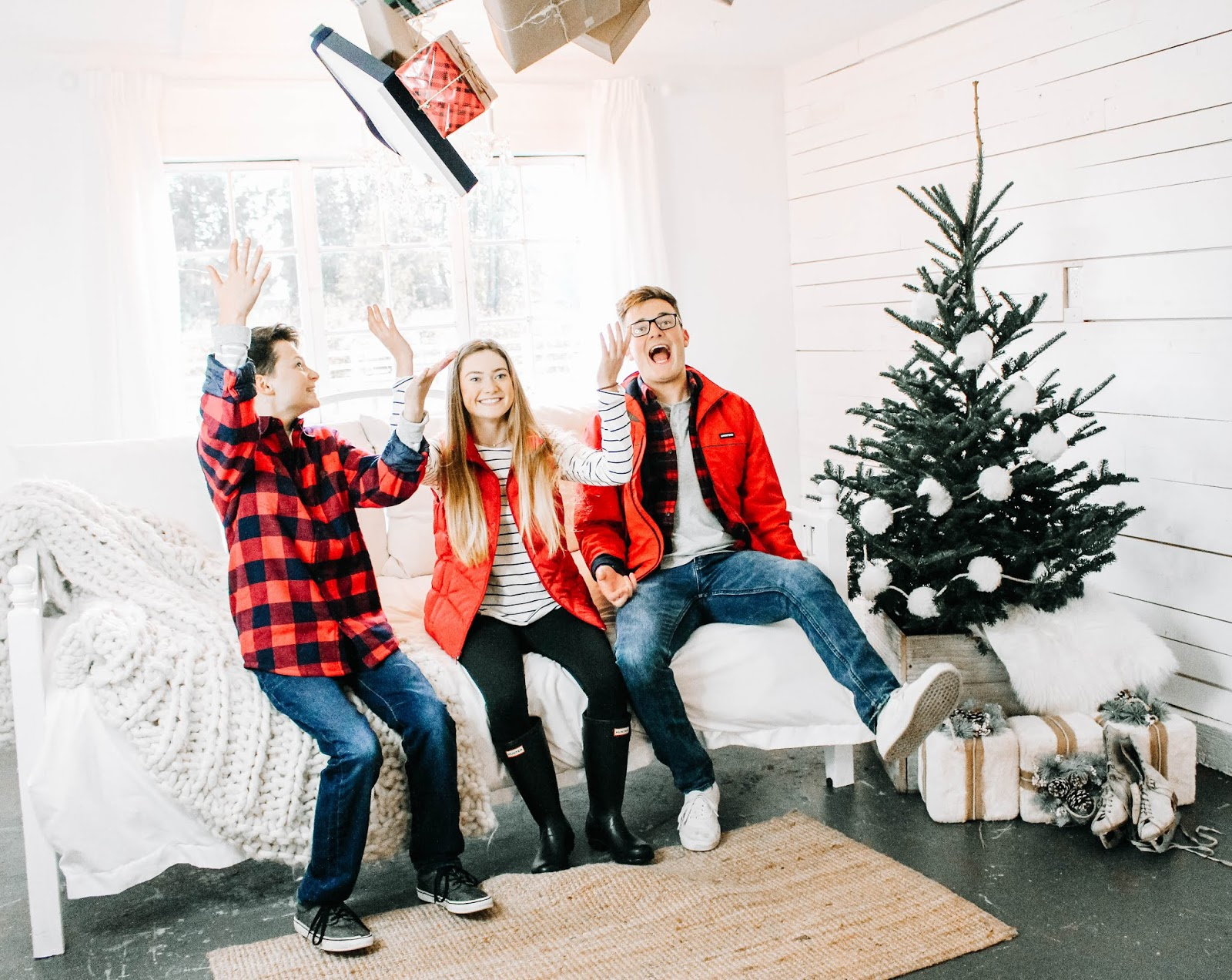kids throwing presents in the air in a white room