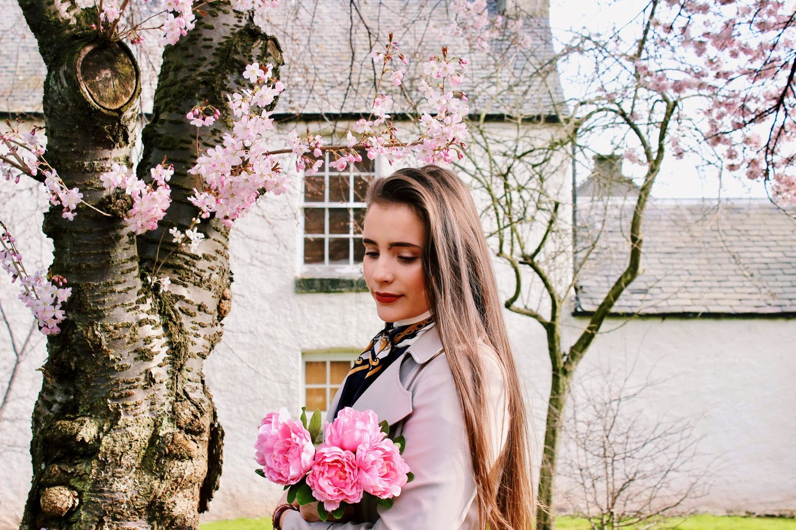 Girl under blooming cherry tree with flowers