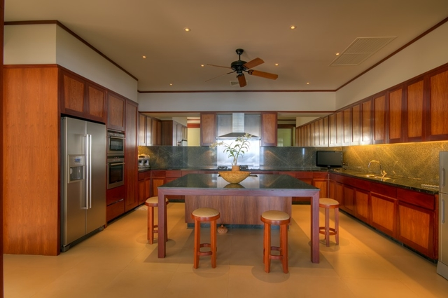 Big kitchen with the island in the middle and round chairs around it