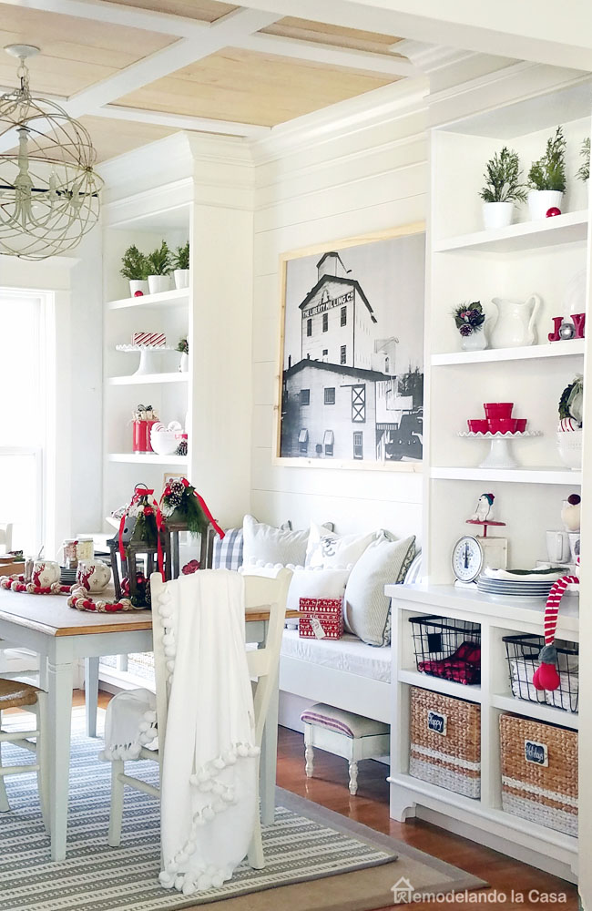 Built-ins in dining room decorated for Christmas with a red and white palette with baskets, white dishes and a bench in between.