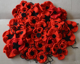 A pile of crocheted poppies of different designs.