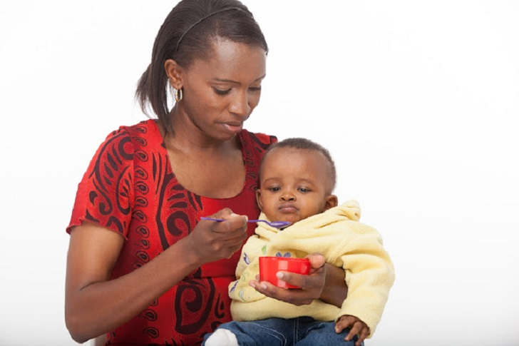 BLACK WOMAN FEEDING HER BABY