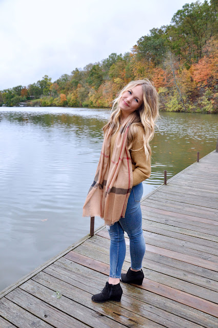 girl smiling on the dock surrounded by fall foliage