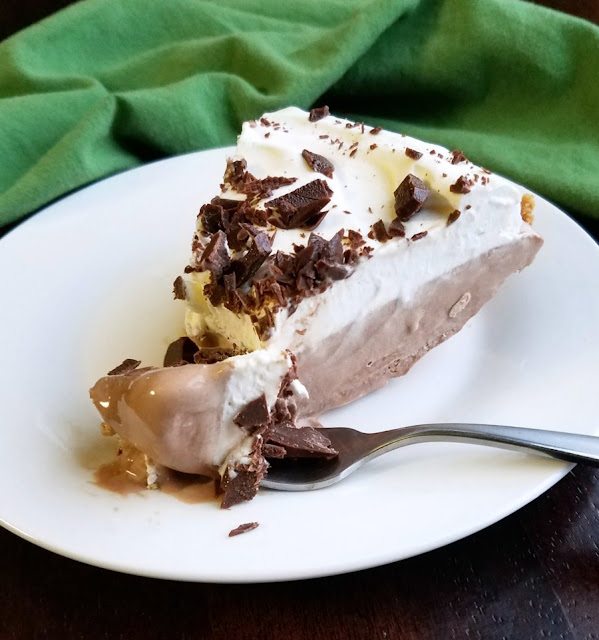 slice of frozen chocolate pie with whipped cream and chopped chocolate mints on top