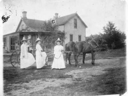 Ladies dressed up standing by horse drawn carriage