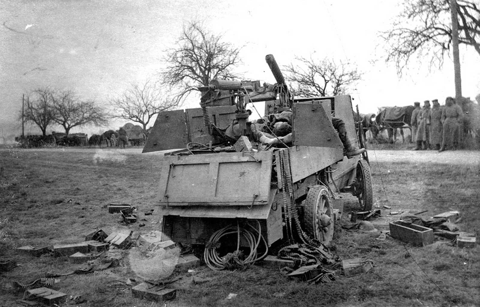 A German column looks over a destroyed Canadian Armored Autocar, the bodies of Canadian soldiers, empty belts, and cartridge boxes strewn about.
