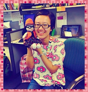 Little Colourful Teacher (Ms A.K.) smiling as she holds up Kwokkie Doll who is modelling the new outfit. Ms A.K. is wearing jeans with a white T-shirt which has stylised pink and blue flowers. A lanyard around her neck has chevron stripes of white alternating with bright colours. Little Colourful Teacher is sitting on an office chair with a desk cubicle behind her.