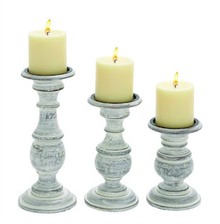 White pillar candles on white candle holders.