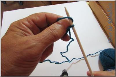 Foto mostrando o polegar sendo retirado da alça de fio que o envolvia para formar um ponto da montagem simples de pontos da base de tricô.