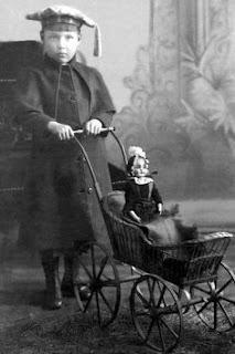 Niño con cochecito de mimbre antiguo