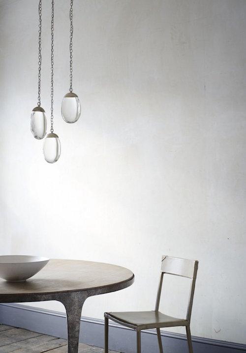 Drei Lampen aus Glas hängen über einem Tisch