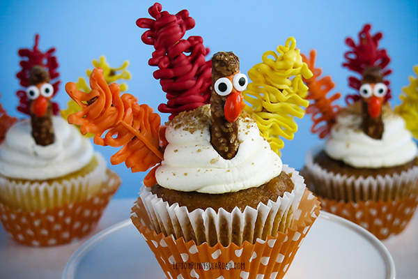 Add candy feathers and faces to cupcakes to make Thanksgiving Turkeys