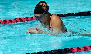 Setting Goals: Image of a young woman swimming breaststroke in the pool
