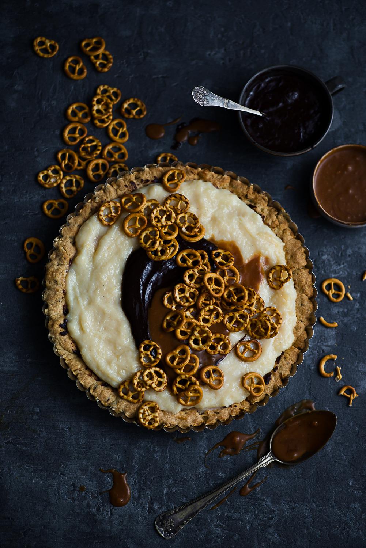 Tarta orzechowa z kremem budyniowym, czekoladą, karmelem i słonymi precelkami
