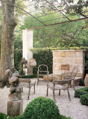Pea gravel and boxwood in a French country courtyard with old stone fountain and ancient chairs. Pamela Pierce Designs.