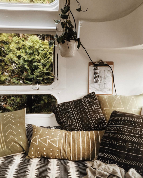 aztec and organic pillows and linen patterns on a daybed of a vintage airstream