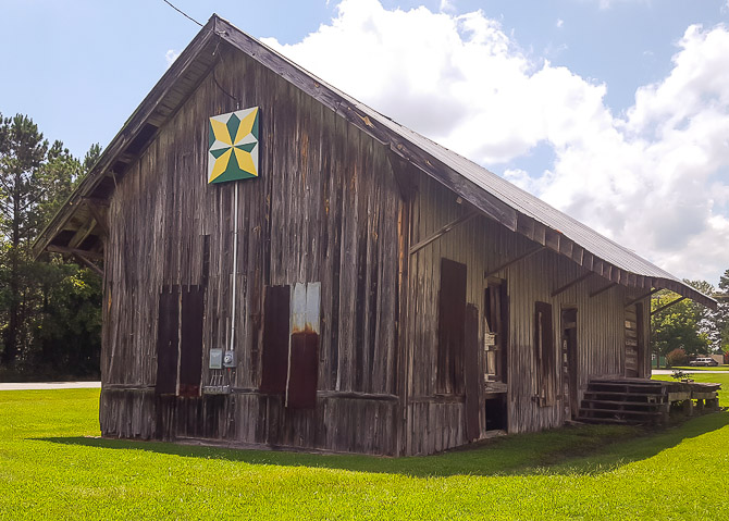 Colorful barn quilt on old building