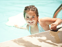 Image of Young Happy Girl in the water at the edge of the pool:Best Swimming Tips - Have Fun