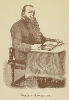 Abraham Tuominiemi piirroksena, joka todennäköisesti perustuu valokuvaan. Tukeva mies, jolla on pitkä parta, istuu pöydän ääressä kirja edessään