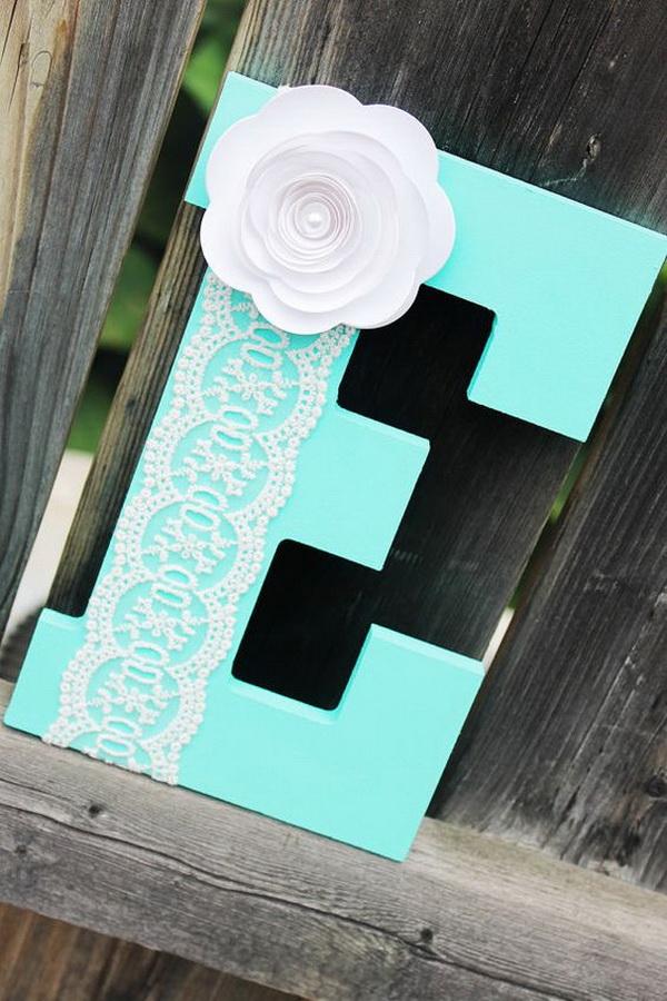Escolha uma cor que você ame e que seja vibrante, depois pinte uma leta de madeira e decore com delicados ornamentos de papel! Pode ser um presente original e barato para o bebê de sua amiga!