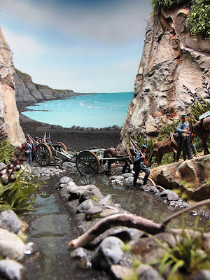 Diorama of 19th-century soldiers crossing a creek by the sea.