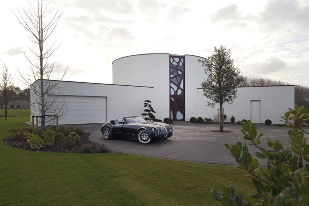 Photo of modern white villa with black car parked on the driveway