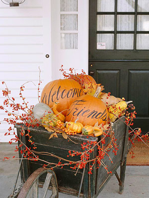 These pumpkins in a wheelbarrow welcoming friends into the home are festive.