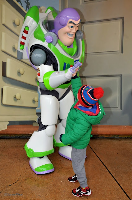 A little boy giving Buzz Lightyear a high-five