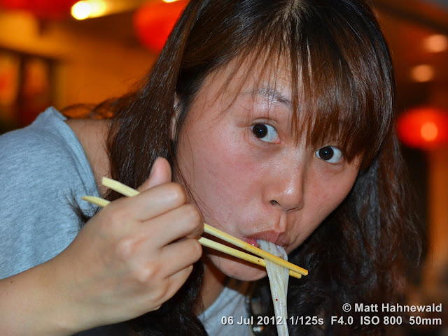 China, Beijing, Donghuamen night market, portrait, Chinese woman eating bizarre food, Chinese woman slurping noodles, Chinese food delicacies, chop sticks
