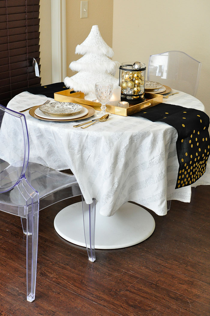 An eclectic holiday tour of a small apartment living and dining space decorated for Christmas! The black, white, gold and silver touches are gorgeous.