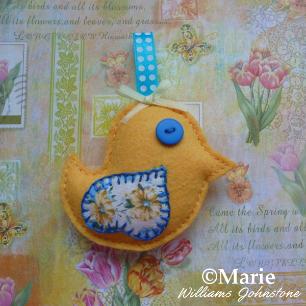 Bright yellow felt bird Spring Easter chick design with blue accents on a floral background craftymarie craft
