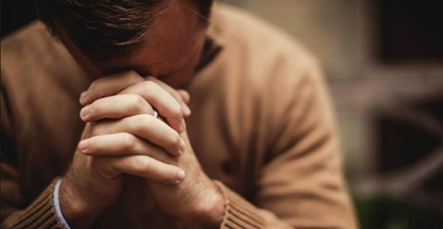 melipat tangan dan menunduk berdoa