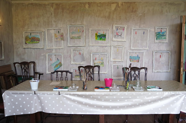 the art room at allan bank, a long table with old chairs in front of a wall of paintings