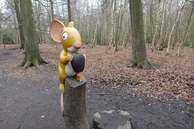 A wooden carved large mouse from The Gruffalo holding a large nut