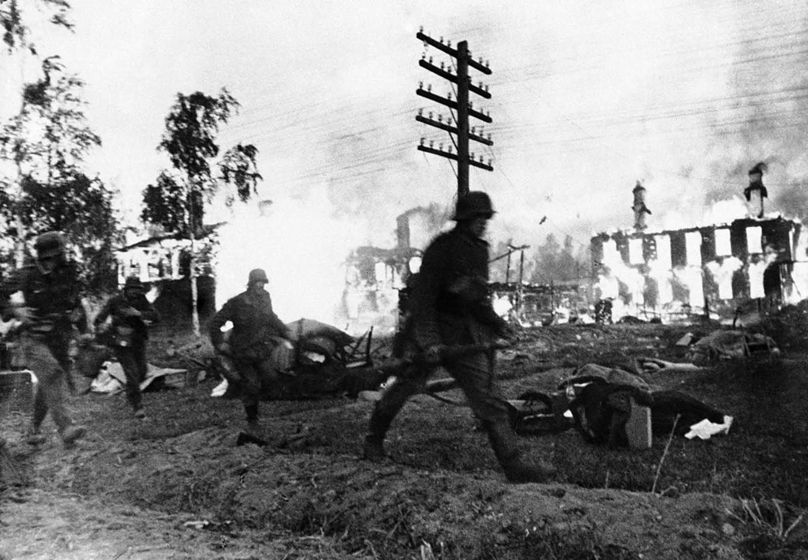 German troops make a hasty advance through a blazing Leningrad suburb, in Russia on November 24, 1941.