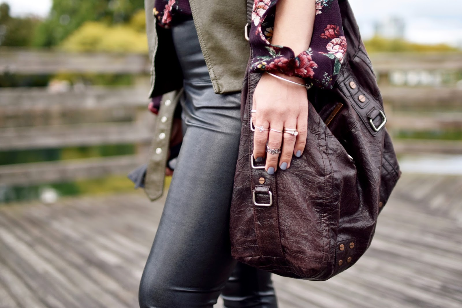 Monika Faulkner outfit inspiration - split-sleeve floral blouse, vegan leather leggings, moto vest, matt & nat satchel