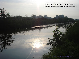 Sun and clouds refelcting in a strip of water surrounded by trees. With wording: Mirror what you want to see, Model who you want to become
