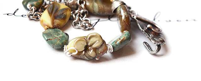 fabricated metal clasp has been worked in mixed and sterling as well as pure silver handcrafted glass beads in simplistic raised flower