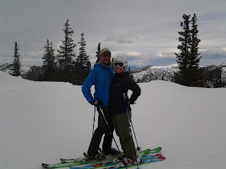 A couple skiing, posing for the camera with trees and mountains in the background.