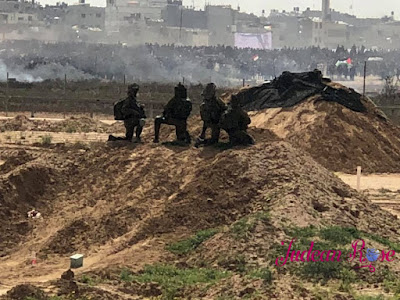 three IDF soldiers look at Gaza from the border