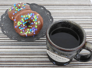 Chocolate frosted doughnuts with sprinkles and coffee