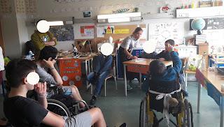 Vários alunos na sala observam uma experiência que está a ser descrita pela professora; um aluno em cadeira de rodas levanta o braço para tirar dúvidas.