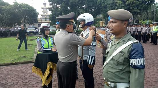 Kapolres Asahan Saat memasangkan Pita Kepada Petugas Yang terlibat Patuh Toba.