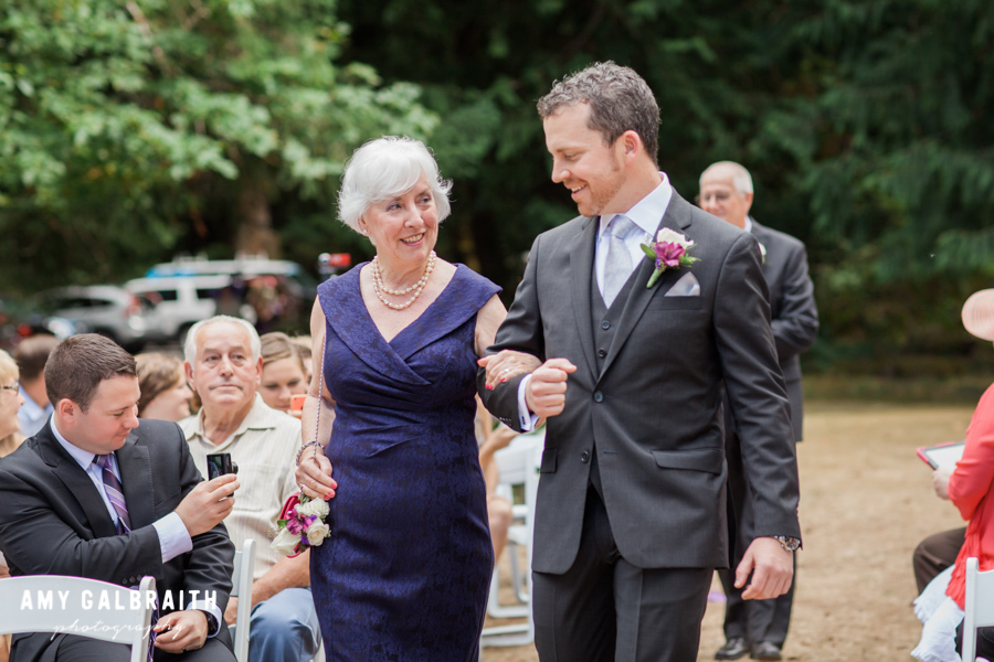 groom escorting his mother down the aisle at a wedding ceremony